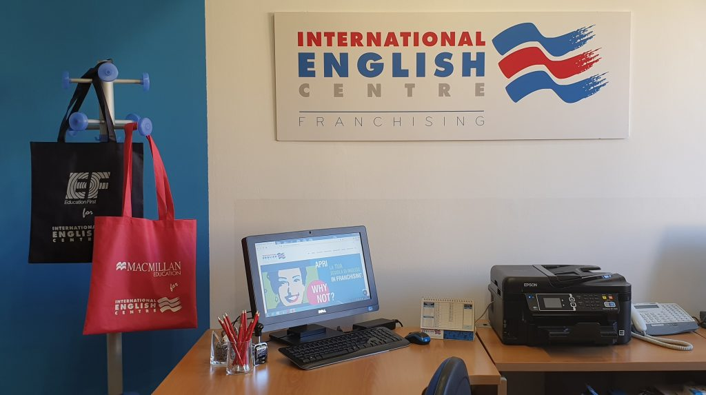 I partner IEC: EF Edication First & Macmillan Education (vista dell'ufficio della Casa Madre Internationa English Centre: appendiabiti con shopper cobrandizzate EF e Macmillan Education, insegna con logo International English Centre, scrivania con PC, portamatite e oggetti vari).