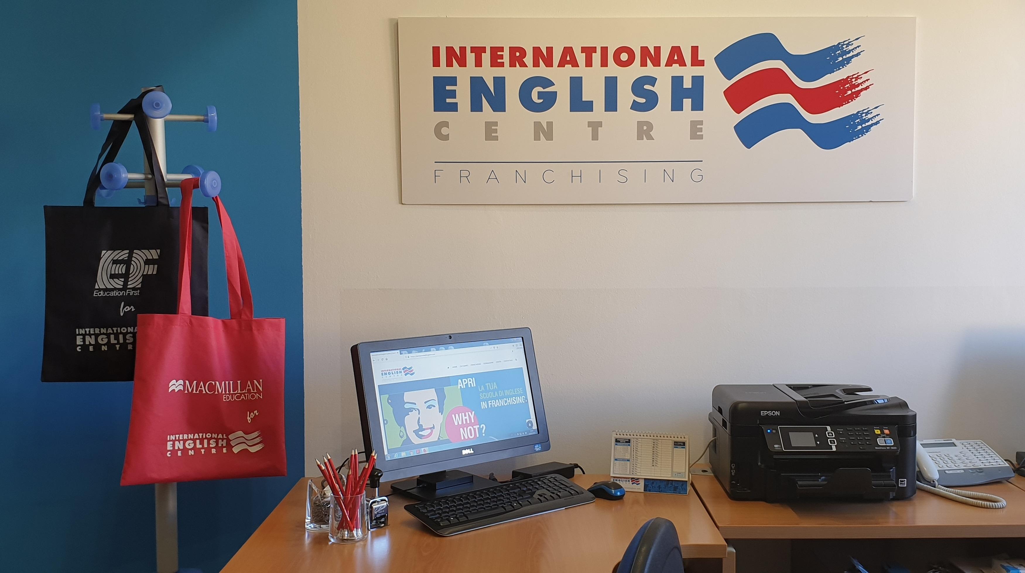 I partner IEC: EF Edication First & Macmillan Education (vista dell'ufficio della Casa Madre Internationa English Centre: appendiabiti con shopper cobrandizzate EF e Macmillan Education, insegna con logo International English Centre, scrivania con PC, portamatite e oggetti vari).