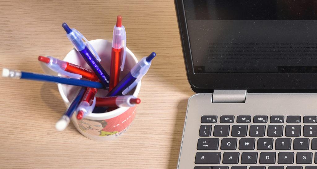 Immagine dell'alto di un laptop su una scrivania con una tazza sponsorizzata IEC sul lato sinistro