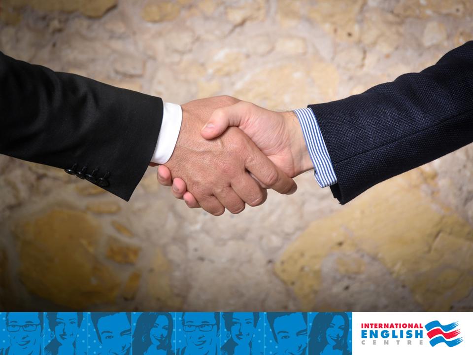Foto che ritrae una stretta di mano tra uomini d'affari, e nella parte in basso della foto sono riportati dei visi blu pop up caratteristici di International English Centre e il logo IEC